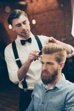 Barber shop classy dressed handsome stylist is doing a perfect h. Airstyle to a bearded guy in caual jeans outfit. Both concentrated and serious stock photography