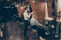 Barber shop classy dressed specialist is styling the hair of a c. Lient. Salon is retro and vintage. Customer is a young bearded man, covered with cape Royalty Free Stock Image