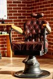 Retro leather chair barber shop in vintage style. Barbershop theme. Barber shop, hairdresser chairs made from brown leather. Retro leather chair barber shop in Stock Photos