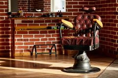 Retro leather chair barber shop in vintage style. Barbershop theme. Barber shop, hairdresser chairs made from brown leather. Retro leather chair barber shop in royalty free stock image