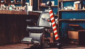 Barber shop pole. Logo of the barbershop, symbol. Stylish vintage barber chair. Hairstylist in barbershop interior royalty free stock images