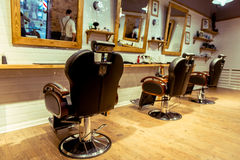 At the barber shop. Stylish barber shop. Designed with white brick and wood. Take care of your hairstyle here Stock Images