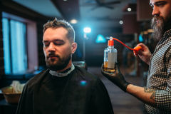 Barber splashing client face by aftershave lotion Stock Images