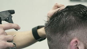 Barber spraying water on the hair of the client stock video