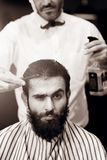 The barber sprinkles on the hair of a young male client of a barber shop with water from a bulb. stock photography
