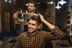Barber standing with morror in front of client Royalty Free Stock Image