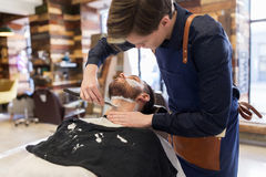Barber with straight razor shaving clients beard. Grooming and people concept - barber with straight razor shaving clients beard at barbershop Royalty Free Stock Photo