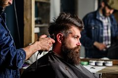 Barber styling hair of brutal bearded client with clipper. Barber with hair clipper works on hairstyle for bearded man. Barber styling hair of brutal bearded stock photo