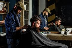 Barber styling hair of brutal bearded client with clipper. Hipster client getting haircut. Barber with hair clipper. Works on hairstyle for bearded men stock photo