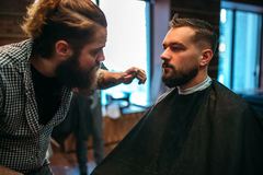 Barber styling mustache and beard at barbershop Stock Photos