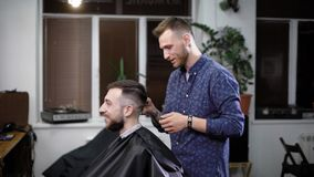 Barber talking to smiling customer while making stylish classic hairdo in salon stock video footage