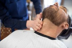 Barber treating male client`s neck at barbershop. Grooming, shaving and people concept - barber treating male client`s neck with balm at barbershop royalty free stock photography