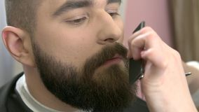 Barber trimming beard, close up. Female hands, comb and scissors. Beard grooming tips for beginners stock footage