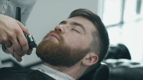 Barber trimming beard with electric razor stock video footage