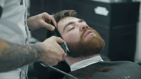 Barber trimming beard with electric razor stock video