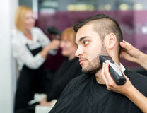 Barber trimming beard with electric razor. Portrait of a men in a barbershop waiting for barber to trim his beard with electric shaver Royalty Free Stock Image
