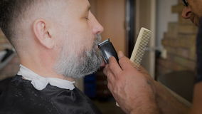 Barber trimming beard to his client. The vintage salon, master serving man. Gray-haired man, and at the age. stock video