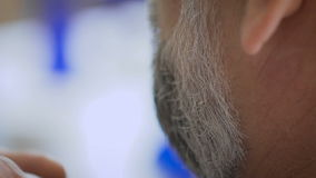 Barber trimming beard to his client. The vintage salon, master serving man. Gray-haired man, and at the age. Slow motion is obtained thanks to a high-speed stock video footage