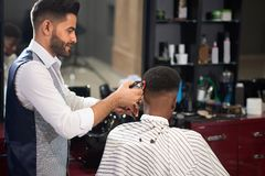 Barber trimming hair of male with clipper in barber shop. Stylish hairdresser in white shirt and waistcoat trimming hair of male client with clipper in barber stock photo