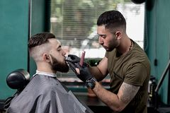 Barber trims mustache of dark-haired stylish man at a barbershop royalty free stock photo