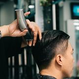 Shaving hair. Barber using electric shaver when doing stylish haircut for the client Royalty Free Stock Image
