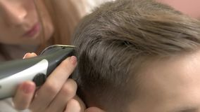 Barber using hair clipper, macro. Work of hairstylist with customer. Hair styling tools reviews stock footage
