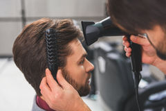 Barber using hairdryer at beauty salon Stock Photos