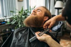 Barber using scissors and comb in barbershop royalty free stock images