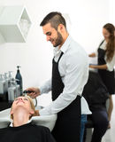 Barber washing customer's hair Royalty Free Stock Images