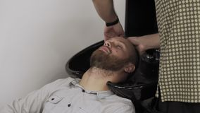 Barber washing hair to bearded man in male salon. Hairdresser wash male head. Barber washing hair to bearded man in male salon. Hairdresser hand wash male head stock footage