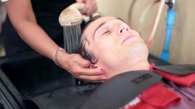 Barber washing hair to young handsome man in male salon. Client in barbershop salon. 1920x1080 stock footage