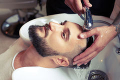 Barber washing man head. In barbershop Stock Photography