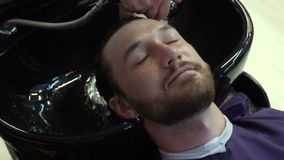 Barber washing man head in barbershop stock video footage