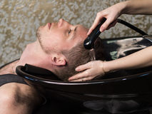 Barber washing man's head Royalty Free Stock Photography