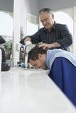 Barber Washing Man's Head. Senior barber washing man's head in hair salon Royalty Free Stock Photos