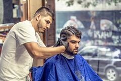 Barber in White Shirt Trimming Man's Hair in Blue Textile While Sitting Nearby Glass Window Royalty Free Stock Photos