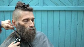 Barber woman carefully trimming beard of client with clipper and comb at outdoor barbershop. Haircutting stock footage