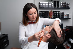 The barber woman shaves beard with razor Stock Images