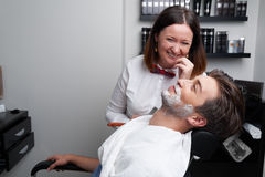 The barber woman shaves beard with razor Royalty Free Stock Images
