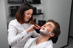 The barber woman shaves beard with razor Stock Photo