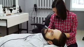 Barber woman trimming beard of client with clipper at barbershop. Barber woman trimming beard of client stock video