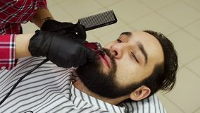 Barber woman trimming beard of client with clipper at barbershop. stock video