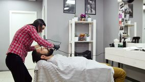 Barber woman trimming beard of client with clipper at barbershop. Barber woman trimming beard of client stock video footage