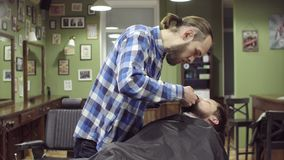 Barber woman trimming beard of client with clipper at barbershop stock footage