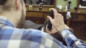 Barber woman trimming beard of client with clipper at barbershop. 4K stock video