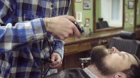 Barber woman trimming beard of client with clipper at barbershop. 4K stock footage