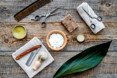 Barber workplace. Shaving brush, razor, foam, sciccors on wooden table background top view Stock Images