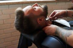 Barberare som rakar med den raka rakkniven för tappning Royaltyfri Bild