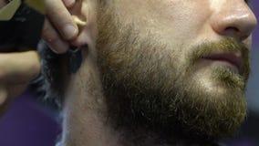 barberare som rakar skägget med rakapparaten lager videofilmer