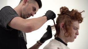 Barberare som rymmer en hårkam och att scissor perfoming av en frisyr för en ljust rödbrun klient arkivfilmer